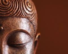 a Buddha face showing only the left eye and ear, referencing meditation