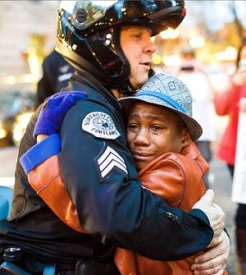 a picture of a young man hugging a riot police officer referencing energy frequency