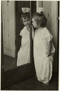 a black-and-white picture of a little girl looking at her reflection in a mirror referencing trust
