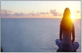 a woman meditating in front of an ocean with the sun on the horizon