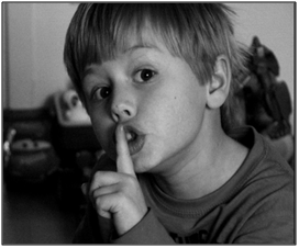 A boy with his finger to his mouth, shushing, referencing mindful meditation