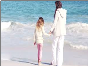 A woman and girl on a beach holding hands, referencing finding love